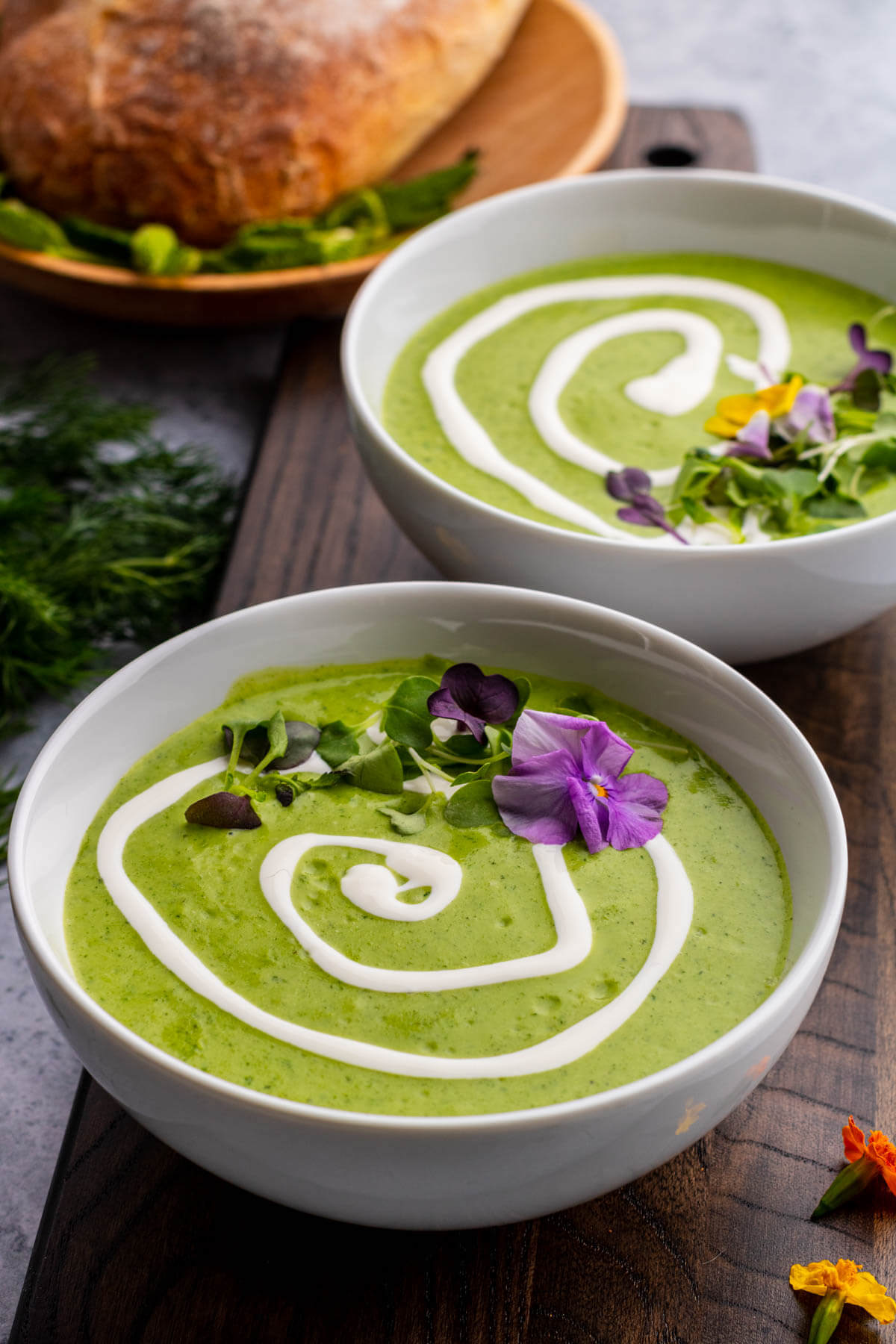 Two bowls of bright green nettle soup with swirls of white cream and microgreen edible flower garnish.
