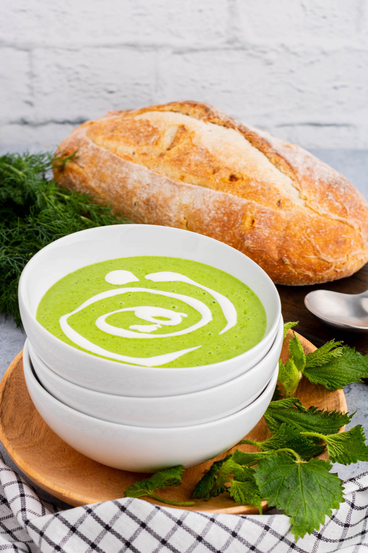 A stack of white bowl with the top containing bright green Nettle Soup garnished with swirls of crème fraiche.