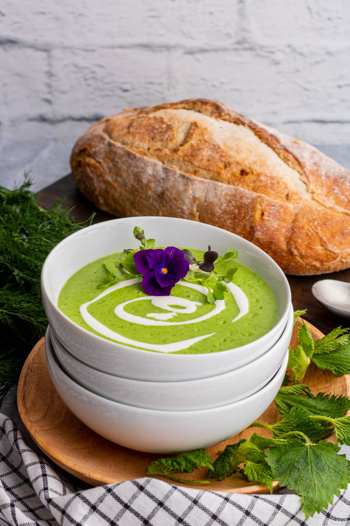 A stack of white bowl with the top containing bright green Nettle Soup garnished with microgreens and edible flowers.