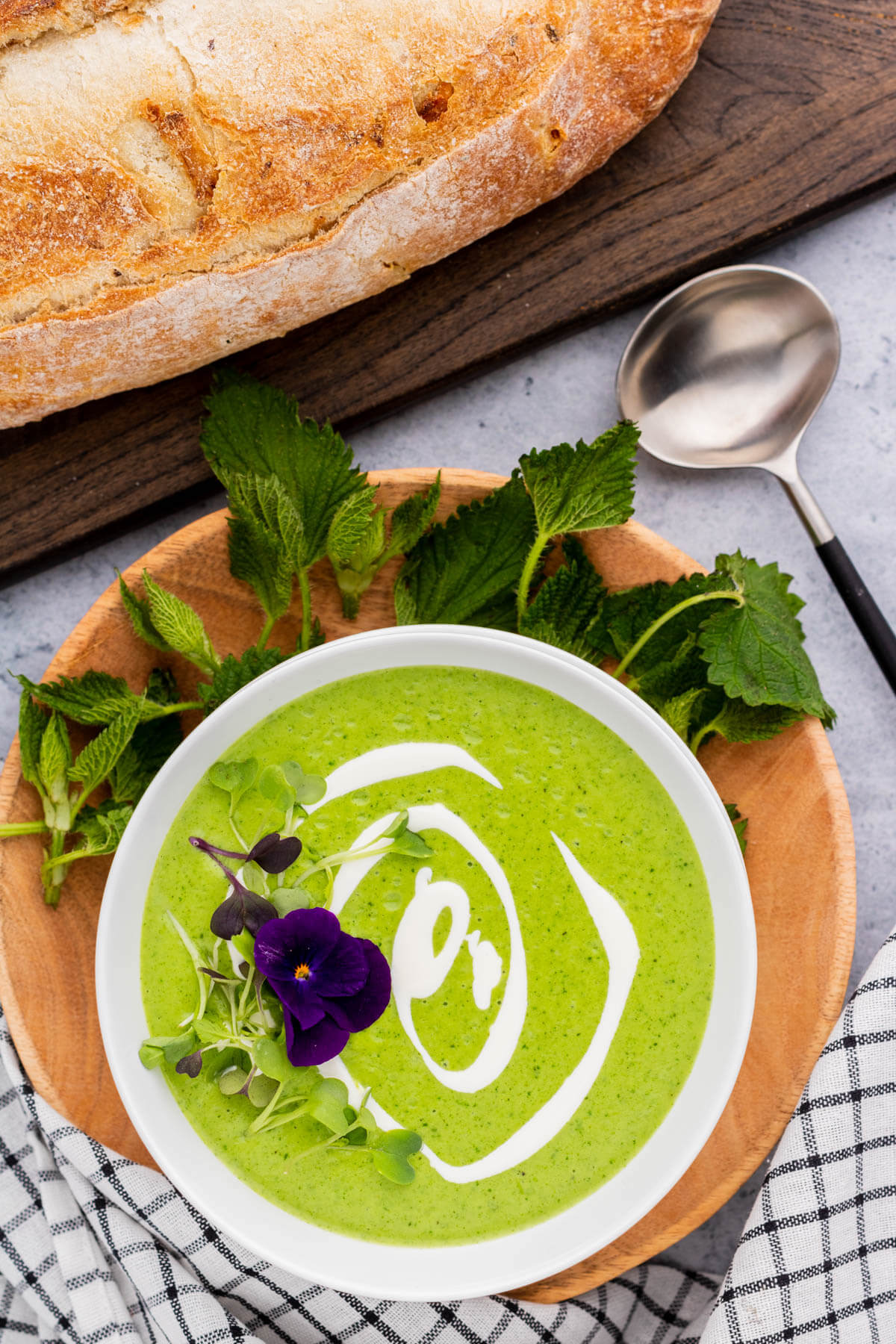 A bowl of bright green nettle soup with swirls of white cream and microgreen edible flower garnish.