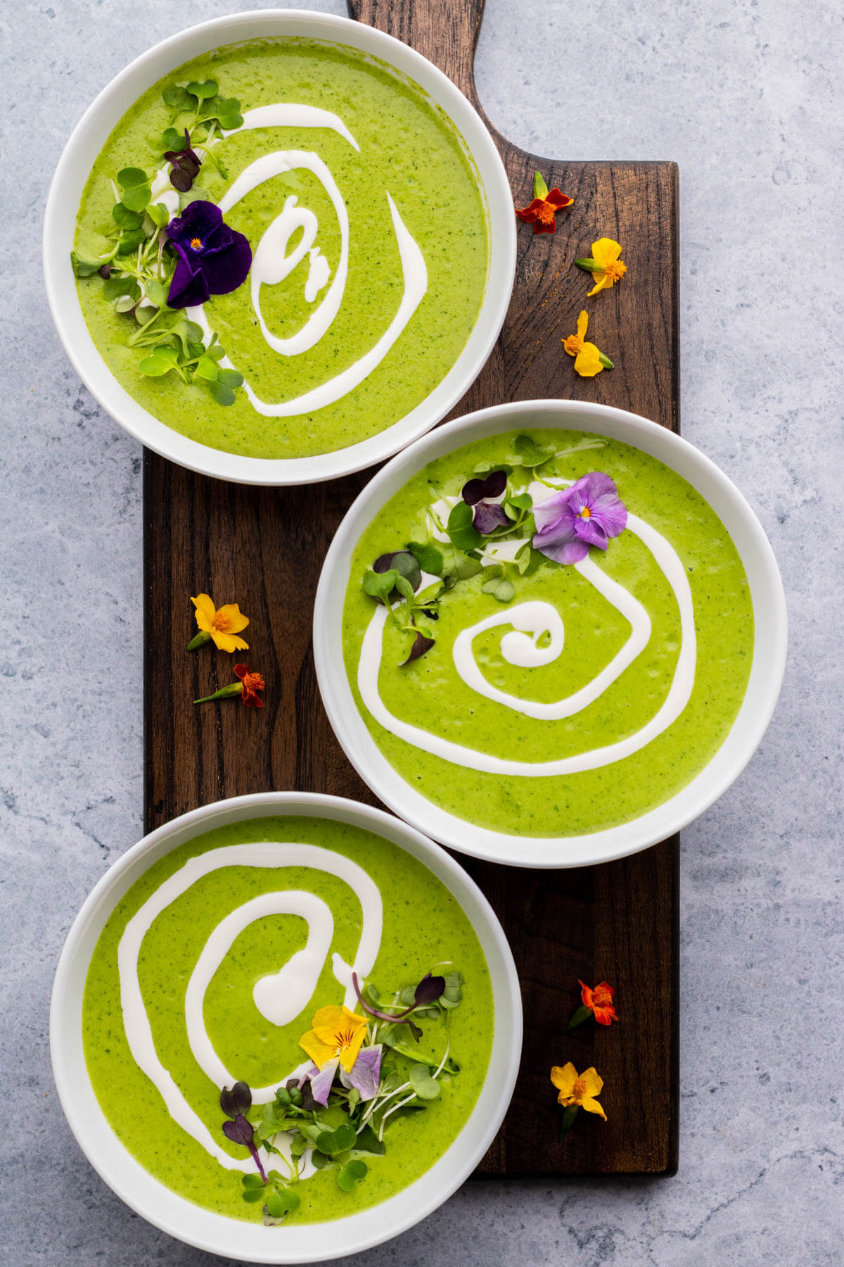 Three bowls of bright green nettle soup with swirls of white cream and microgreen edible flower garnish.
