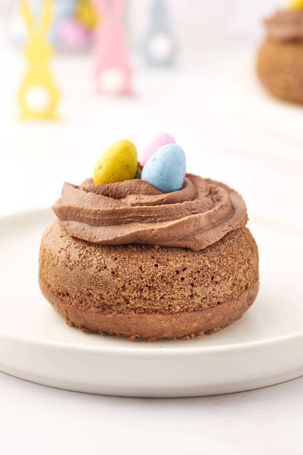 A Chocolate baked donut decorated as an Easter Nest filled with Mini Eggs in an Easter table setting.
