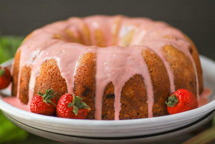 A golden baked bundt cake topped with pink glaze.
