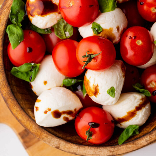 A wooden bowl filled with bright red cherry tomatoes, white mozzarella balls and green basil drizzled with olive oil and balsamic reduction.