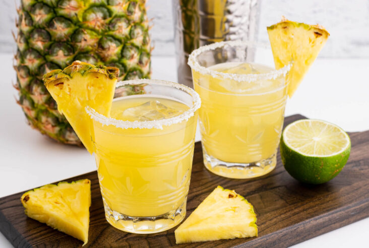 Two rimmed rocks glasses filled with ice and pineapple margarita. Garnished with a slice of pineapple.