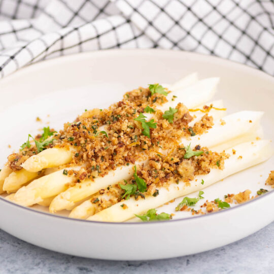 A plate of steamed white asparagus covered in golden pangrattato and herbs.