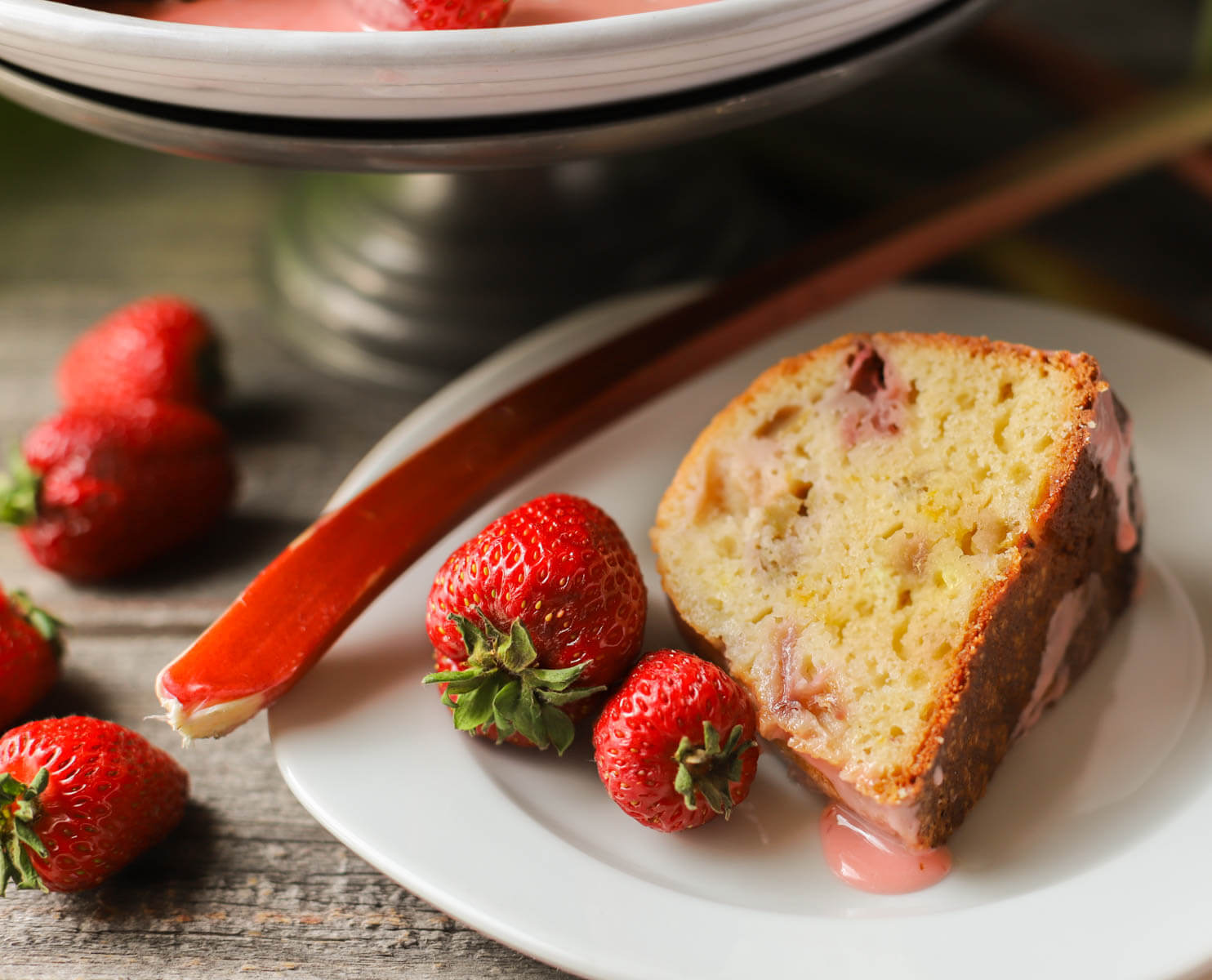 A slice of strawberry rhubarb Greek yogurt cake with strawberries.