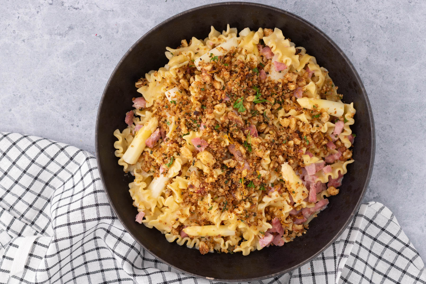 A bowl of lemon butter pasta with ham and white asparagus topped with golden herbed bread crumbs.
