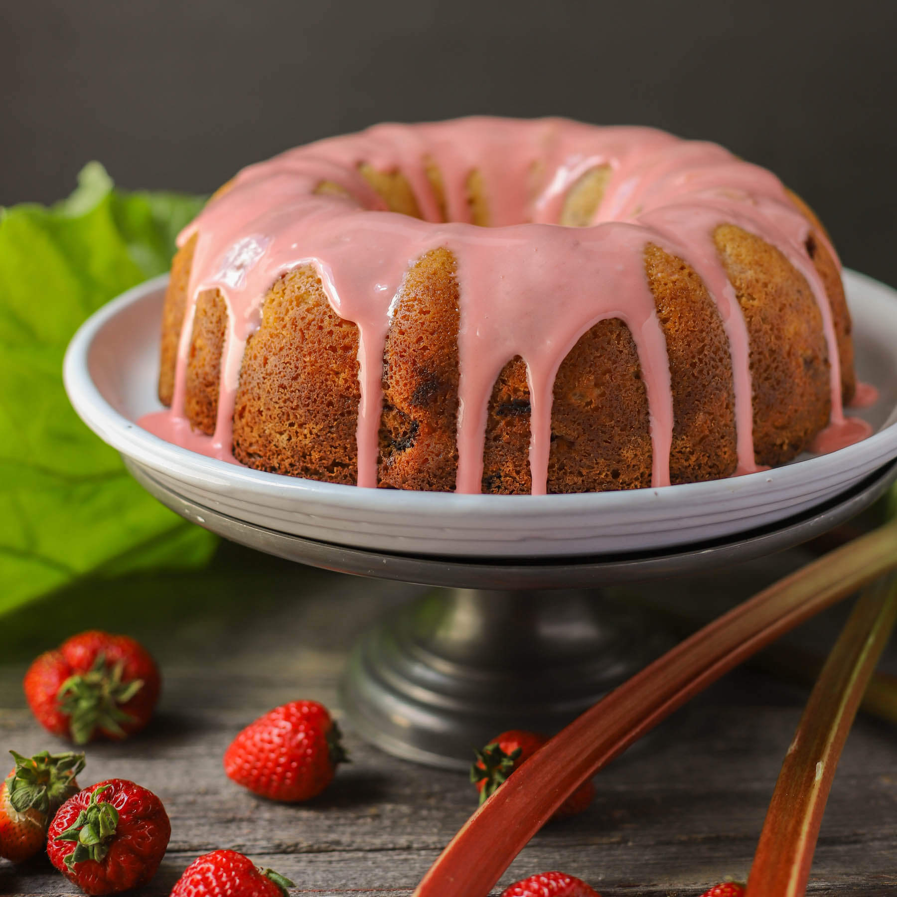 A golden baked bundt cake topped with pink glaze.