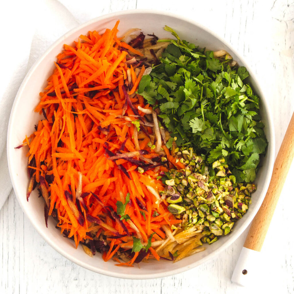 A white bowl filled with carrot salad ingredients before they are mixed together.