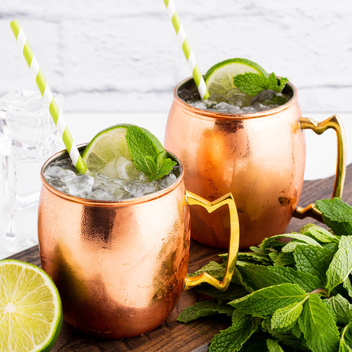 Two icy cocktails in copper mugs surrounded by lime and fresh mint.