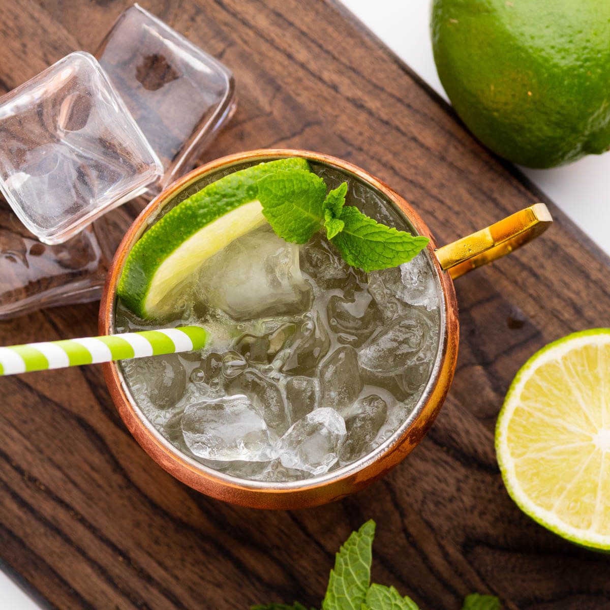 An icy cocktail in a copper mug surrounded by lime and fresh mint.