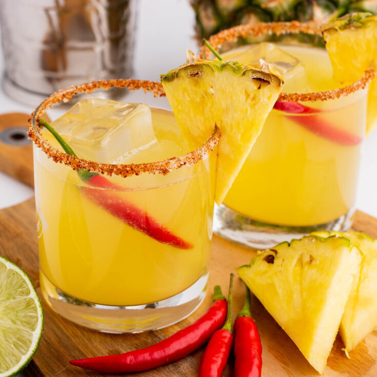 Two Spicy Pineapple Margaritas in red rimmed rocks glasses garnished with a wedge of pineapple and red chili pepper.