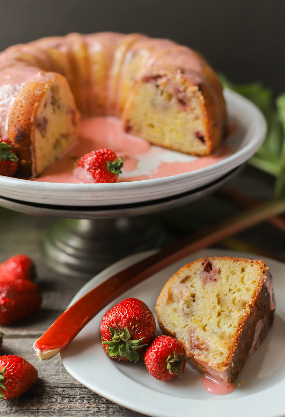 A slice of strawberry rhubarb Greek yogurt cake with the full cake in the background.