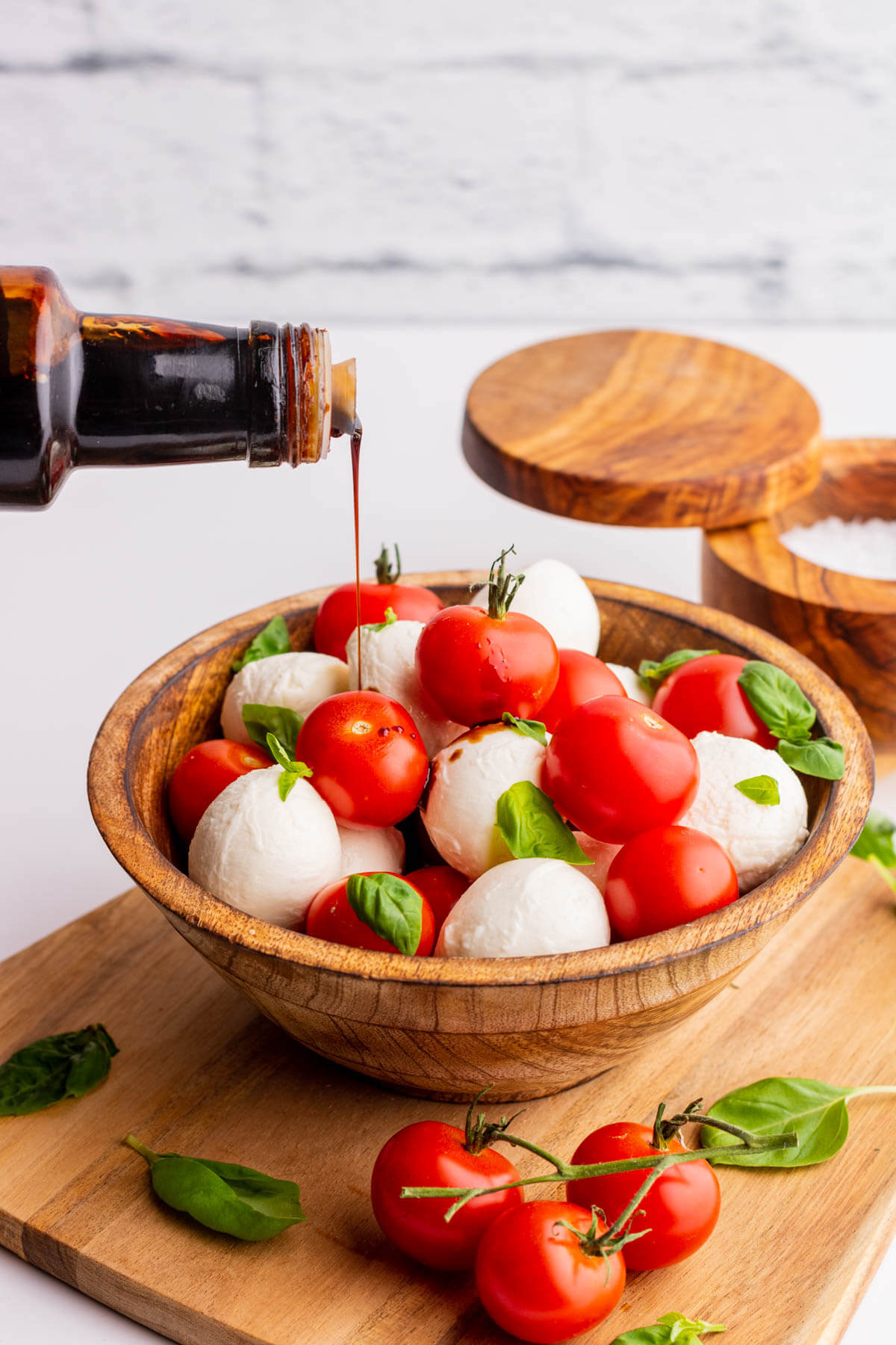 Balsamic vinegar reduction being poured over a red and white Cherry tomato caprese salad.