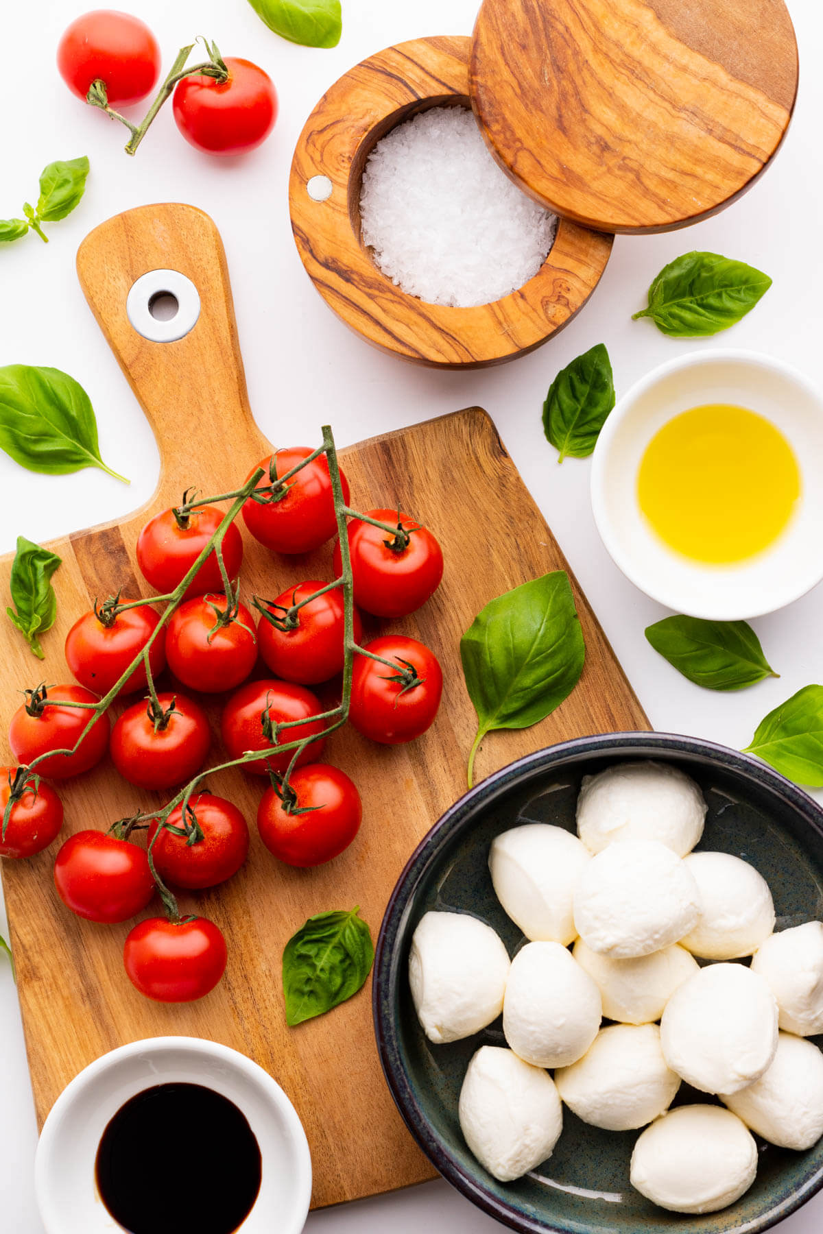 Ingredients needed for a Cherry tomato caprese salad on a wooden cutting board.