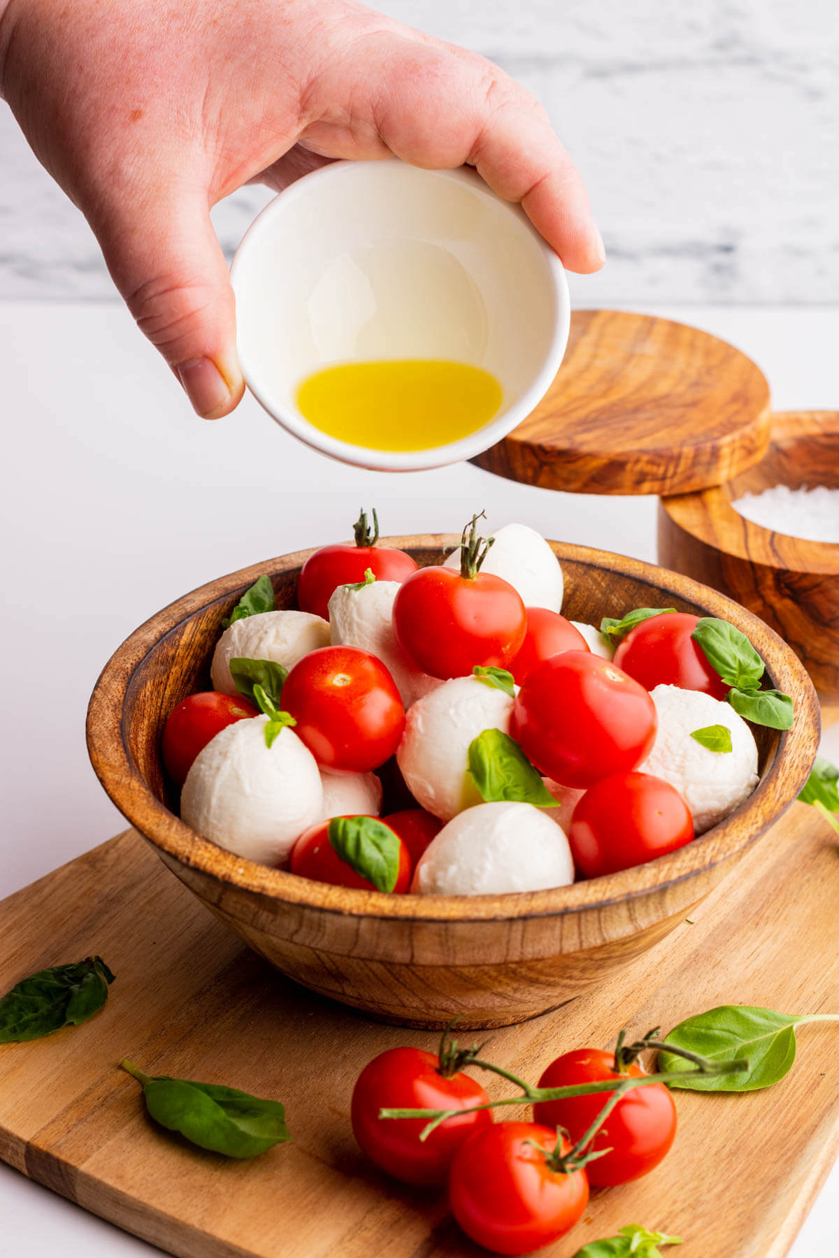 Yellow olive oil being poured over a cherry tomato caprese salad.