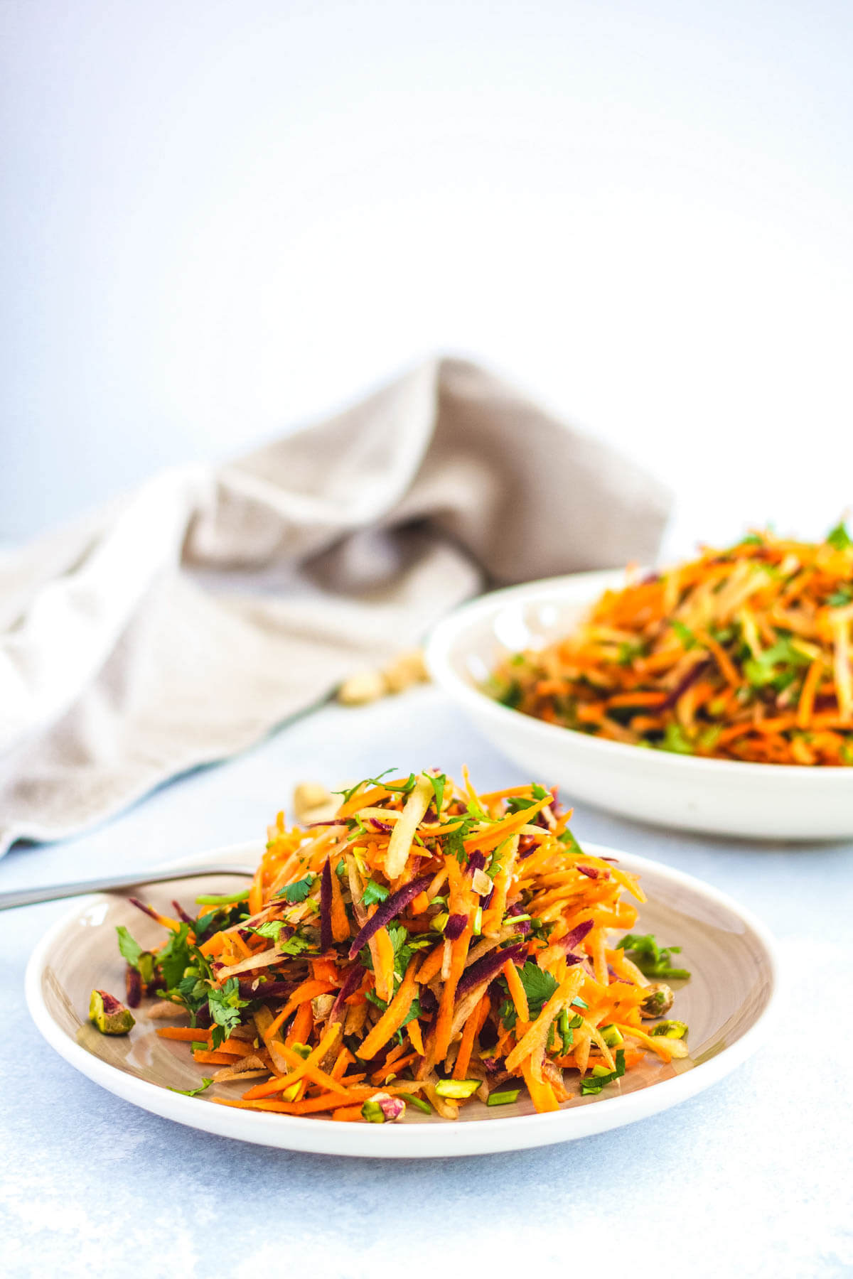 A white plate filled with colourful grated carrot salad.
