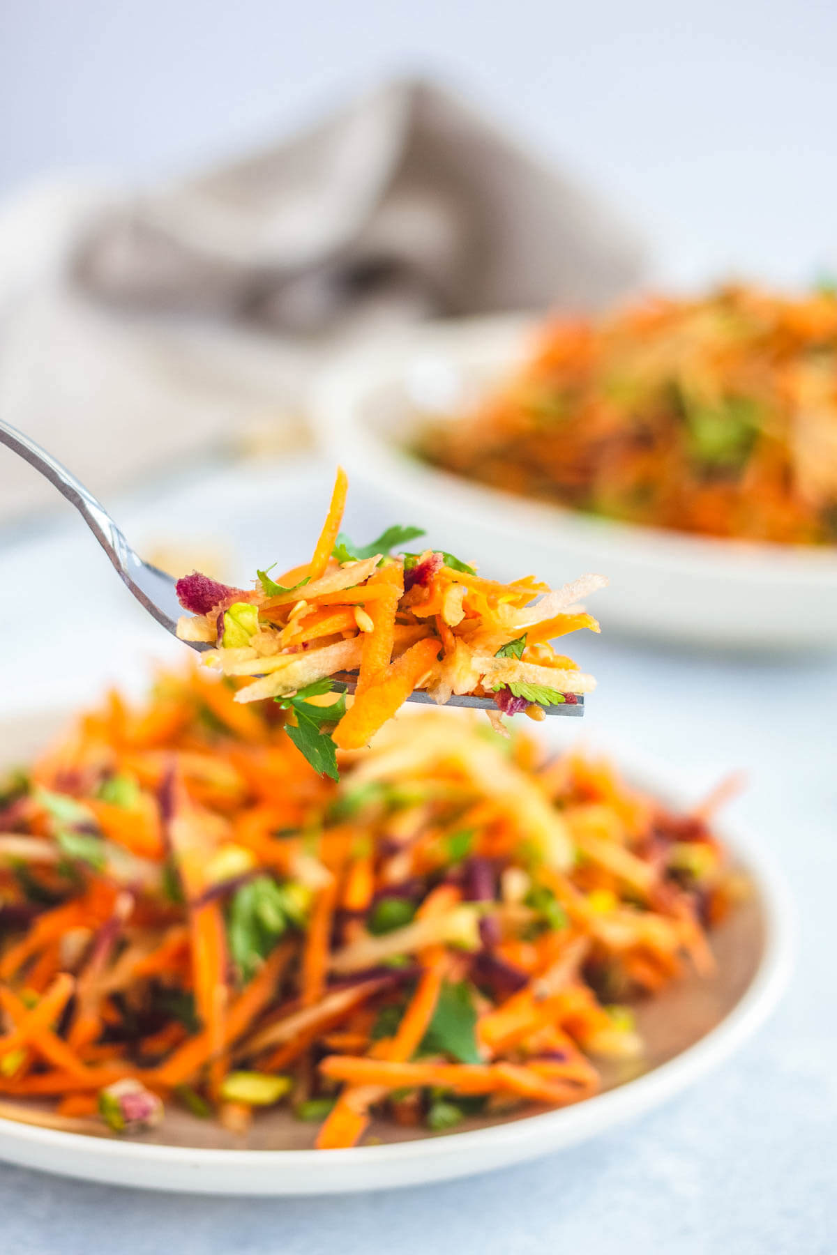 A fork holding colourful carrot salad over a bowl of salad.