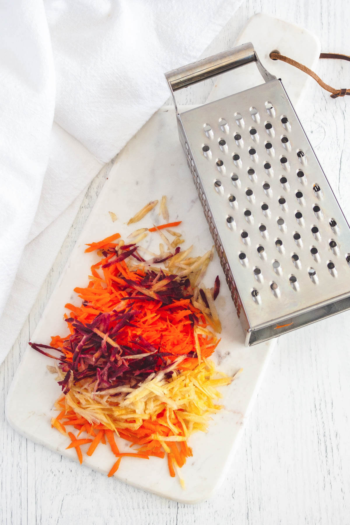 Colourful grated carrots beside a box grater.