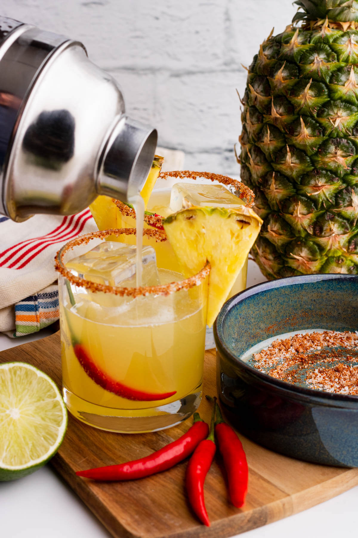 Pouring spicy pineapple margarita into a prepared rocks glass full of ice and a red chili pepper.