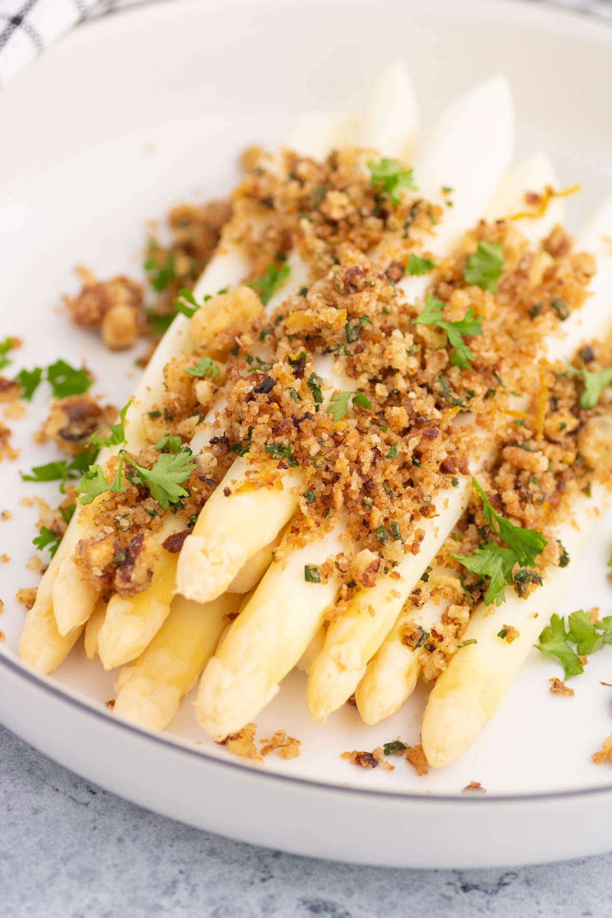 Steamed white asparagus covered in golden pangrattato and herbs.