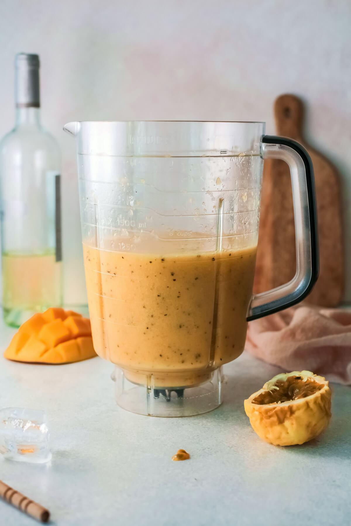 A blender pitcher full of orange coloured mango passionfruit wine slushie.