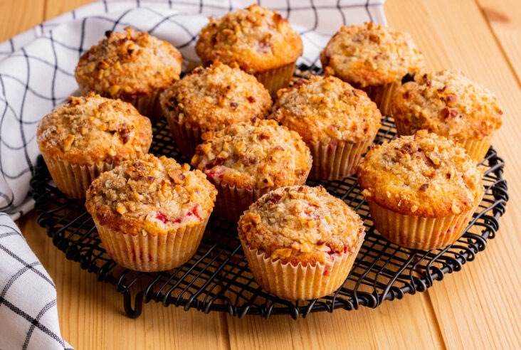 Golden baked strawberry rhubarb muffins cooling on a black round rack.