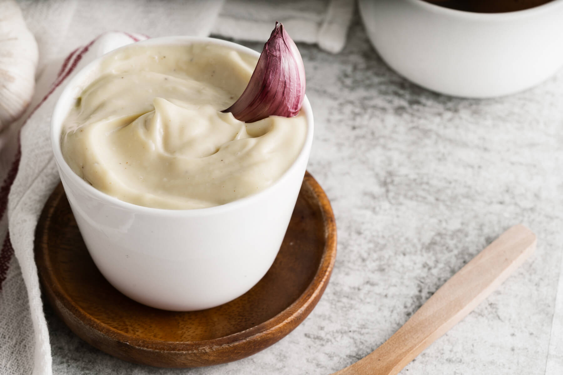 A small white dish filled with creamy Homemade Aioli garnished with a purple clove of garlic.