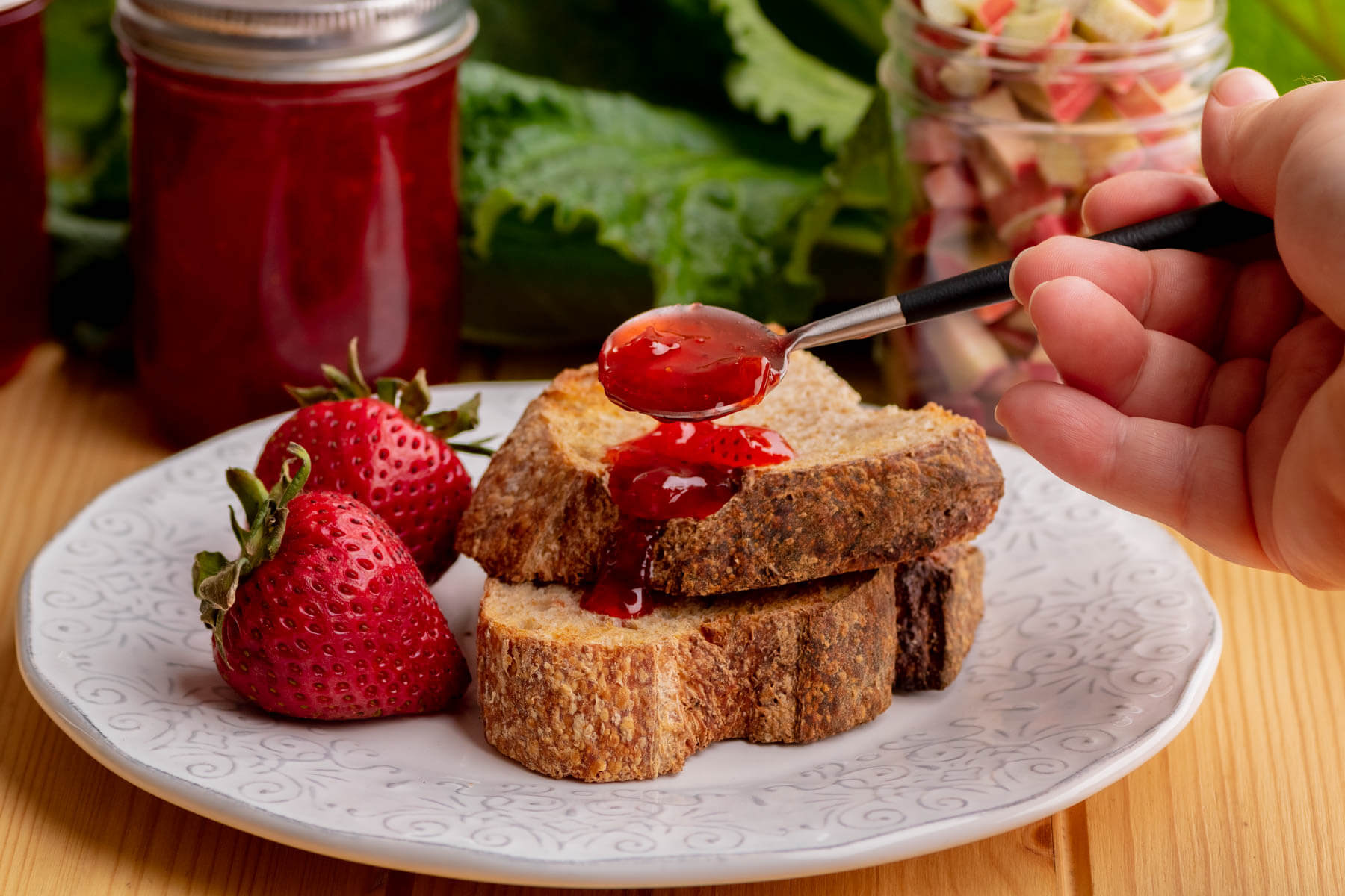 Two sliced of toast slathered in Strawberry Rhubarb Jam with a jar of jam and fresh rhubarb in the background.