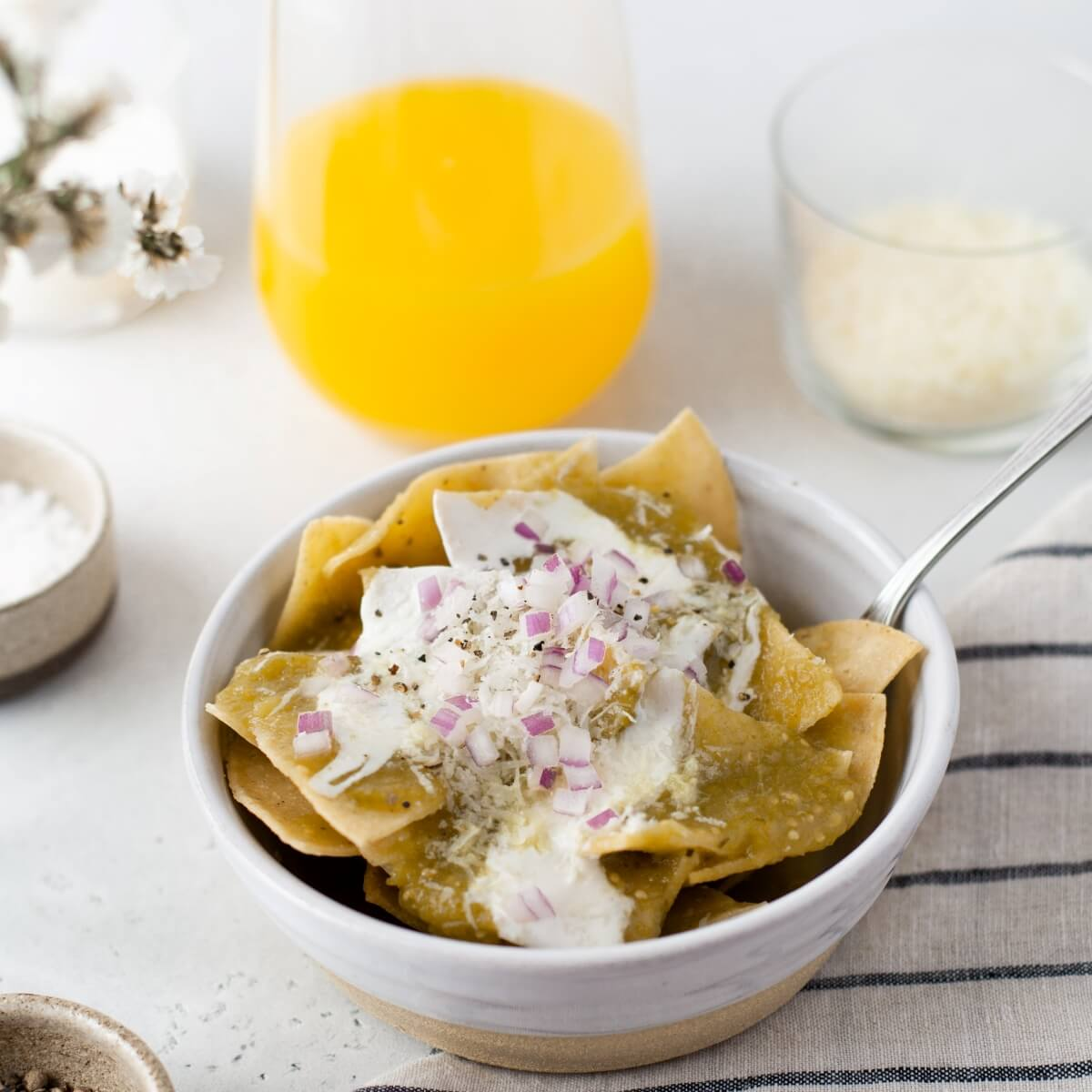 A breakfast setting featuring a bowl of Chilaquiles Verdes topped with sour cream, diced purple onions, cilantro, and cotija cheese.