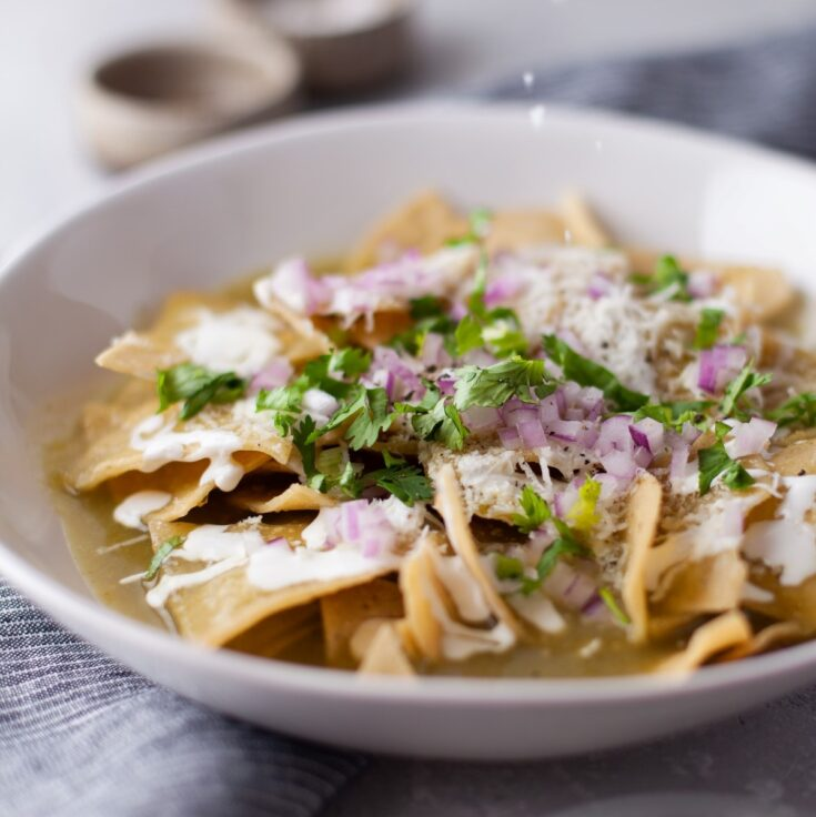 A bowl of Chilaquiles Verdes topped with sour cream, diced purple onions, cilantro, and cotija cheese.