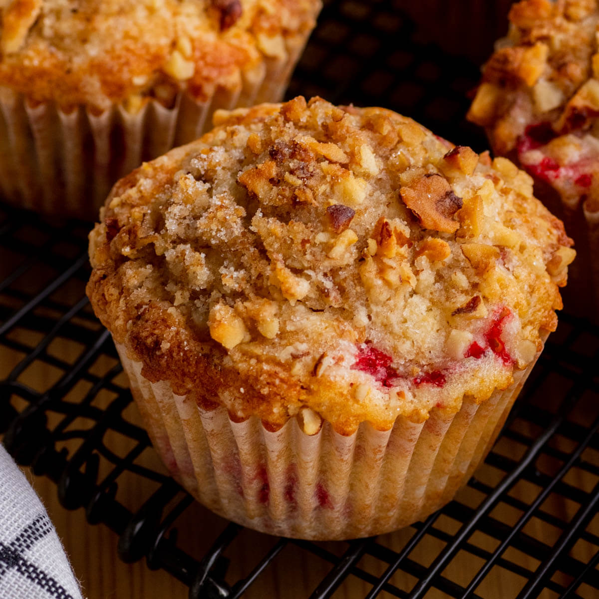 A golden baked strawberry rhubarb muffin topped with streusel.