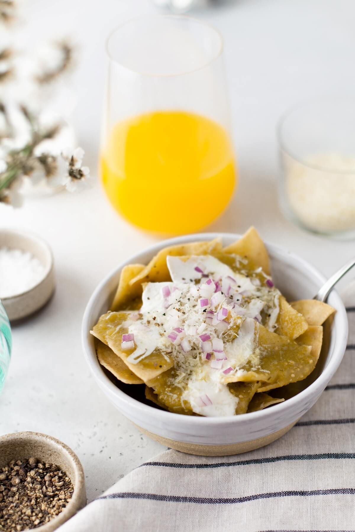 A breakfast table setting featuring a bowl of Chilaquiles Verdes topped with sour cream, diced purple onions, cilantro, and cotija cheese.