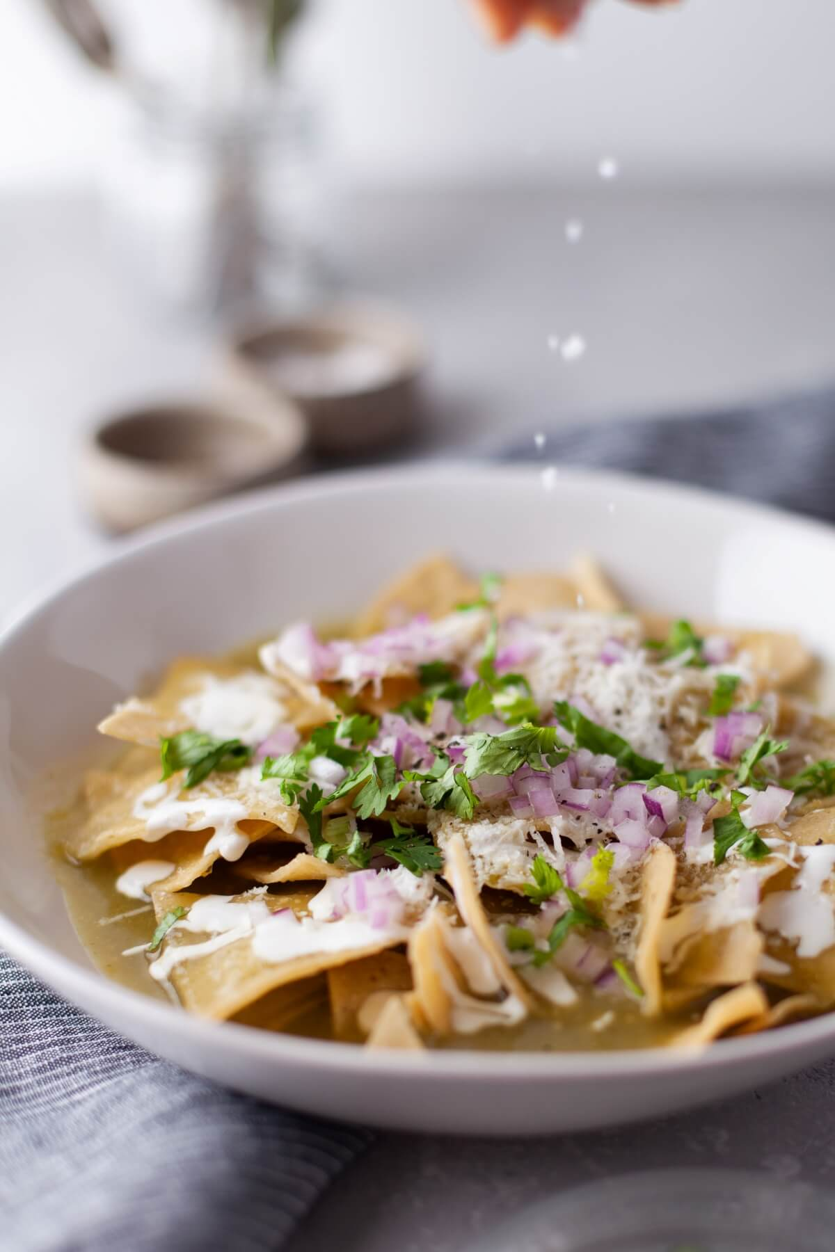 Close up of a bowl of Chilaquiles Verdes being seasoned with salt.