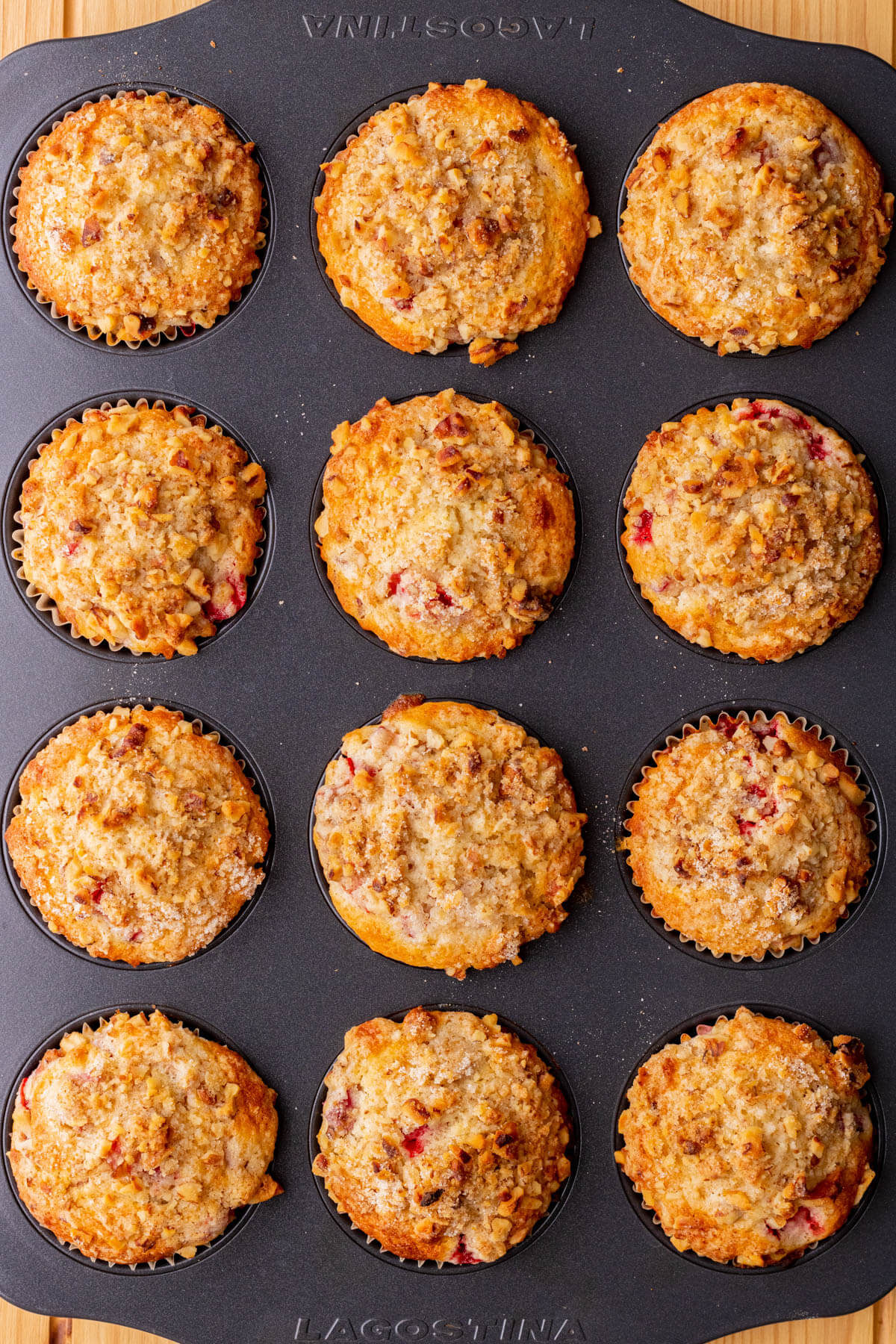 Golden baked strawberry rhubarb muffins in a muffin pan.