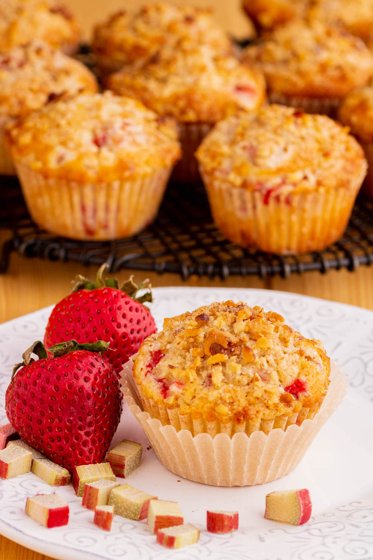 A strawberry rhubarb muffin on a white plate with whole red strawberries and chopped rhubarb.