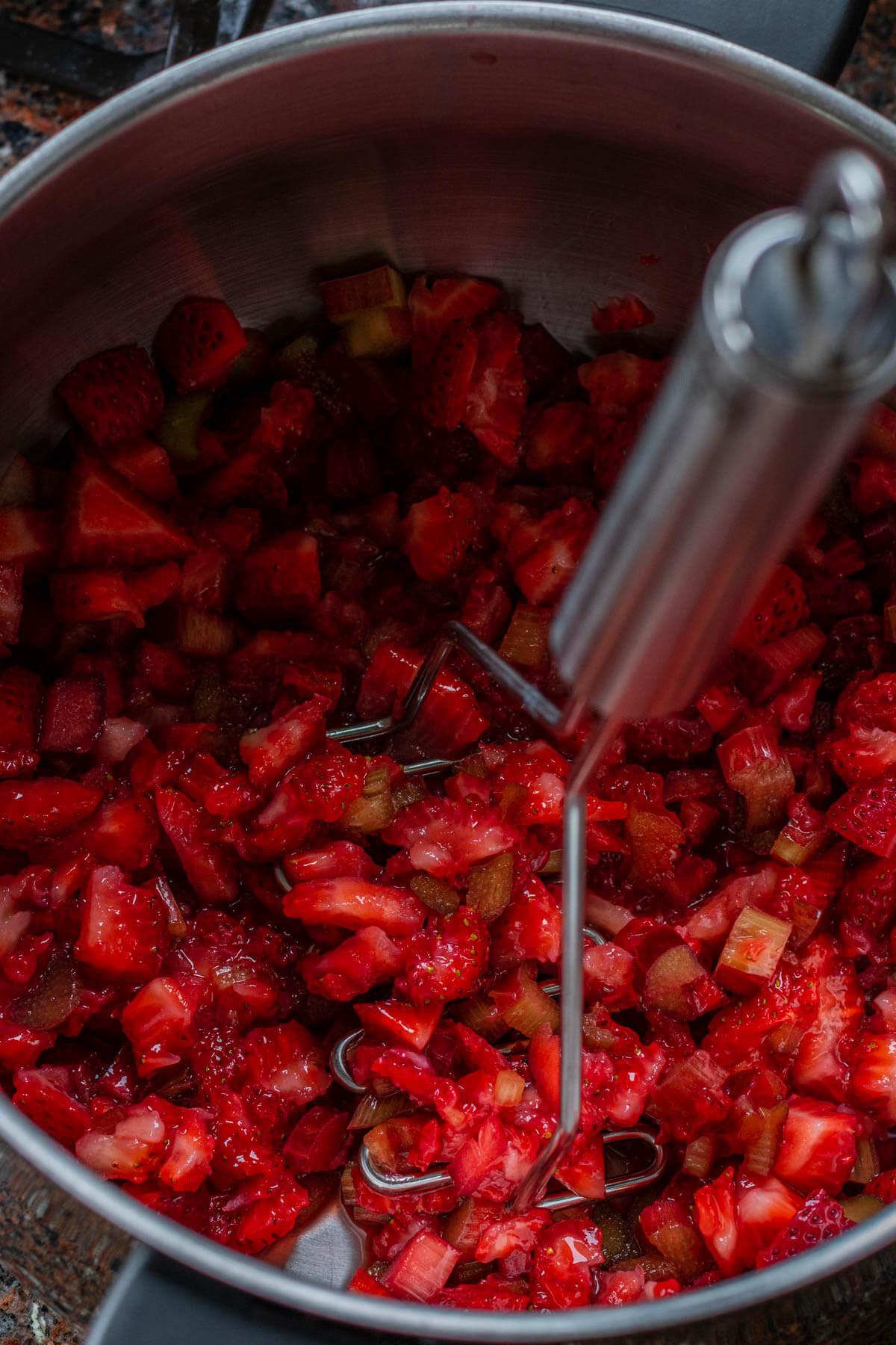 Mashing fresh strawberries with a potato masher in a saucepan.