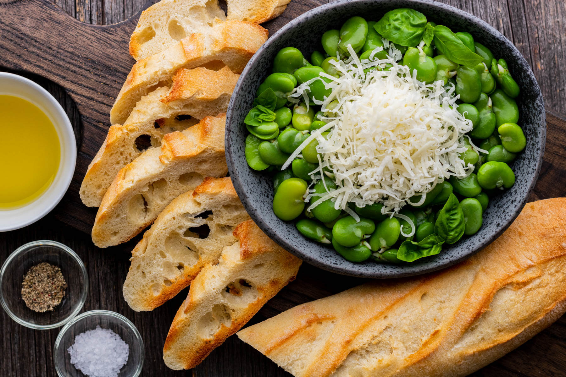 A bowl of bright green fava beans with the ingredients needed to make fava bean crostini.