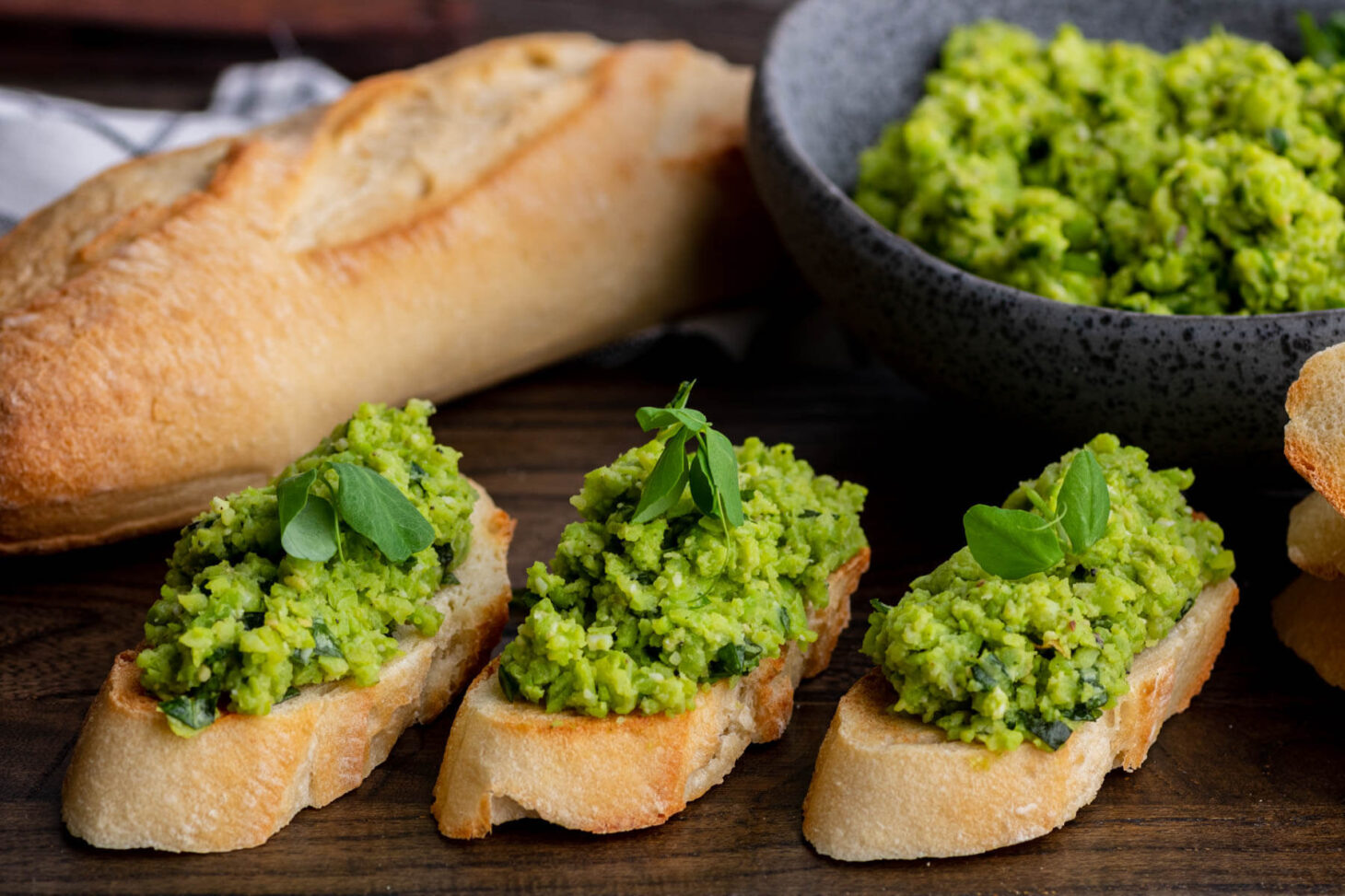 Three fava bean crostini beside a stone bowl filled with fava bean topping and baguette.