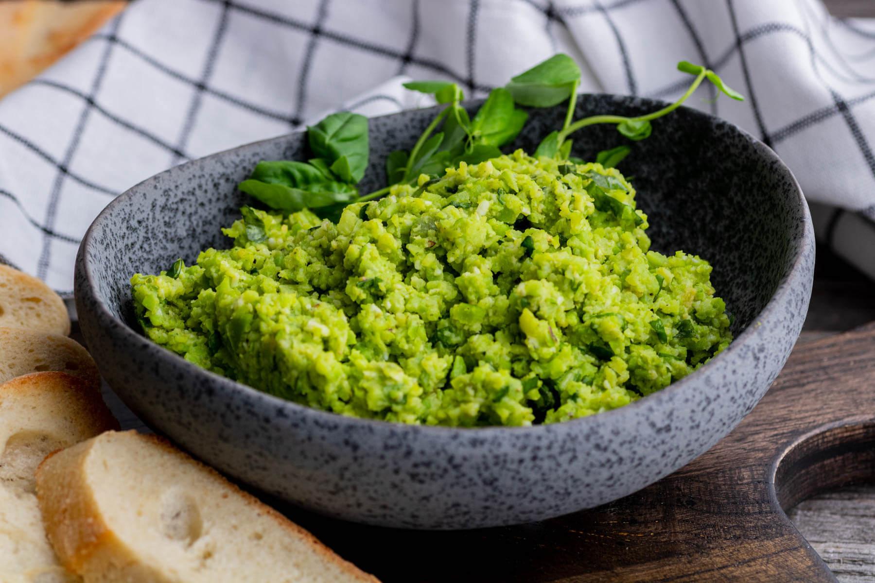 A dark stone bowl filled with bright green fava bean dip.