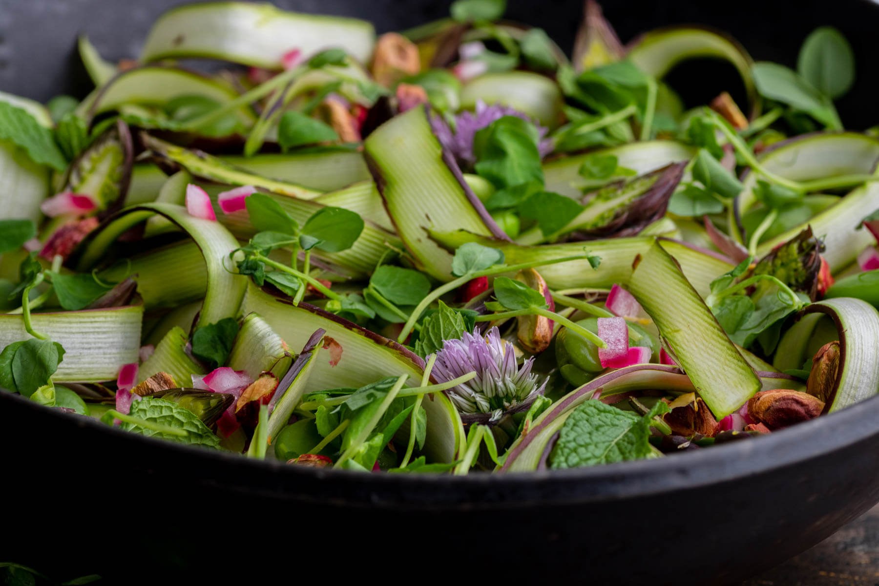 A wide black bowl filled with purple and green shaved asparagus, pistachios, fava beans, fresh herbs and purple chive flowers.