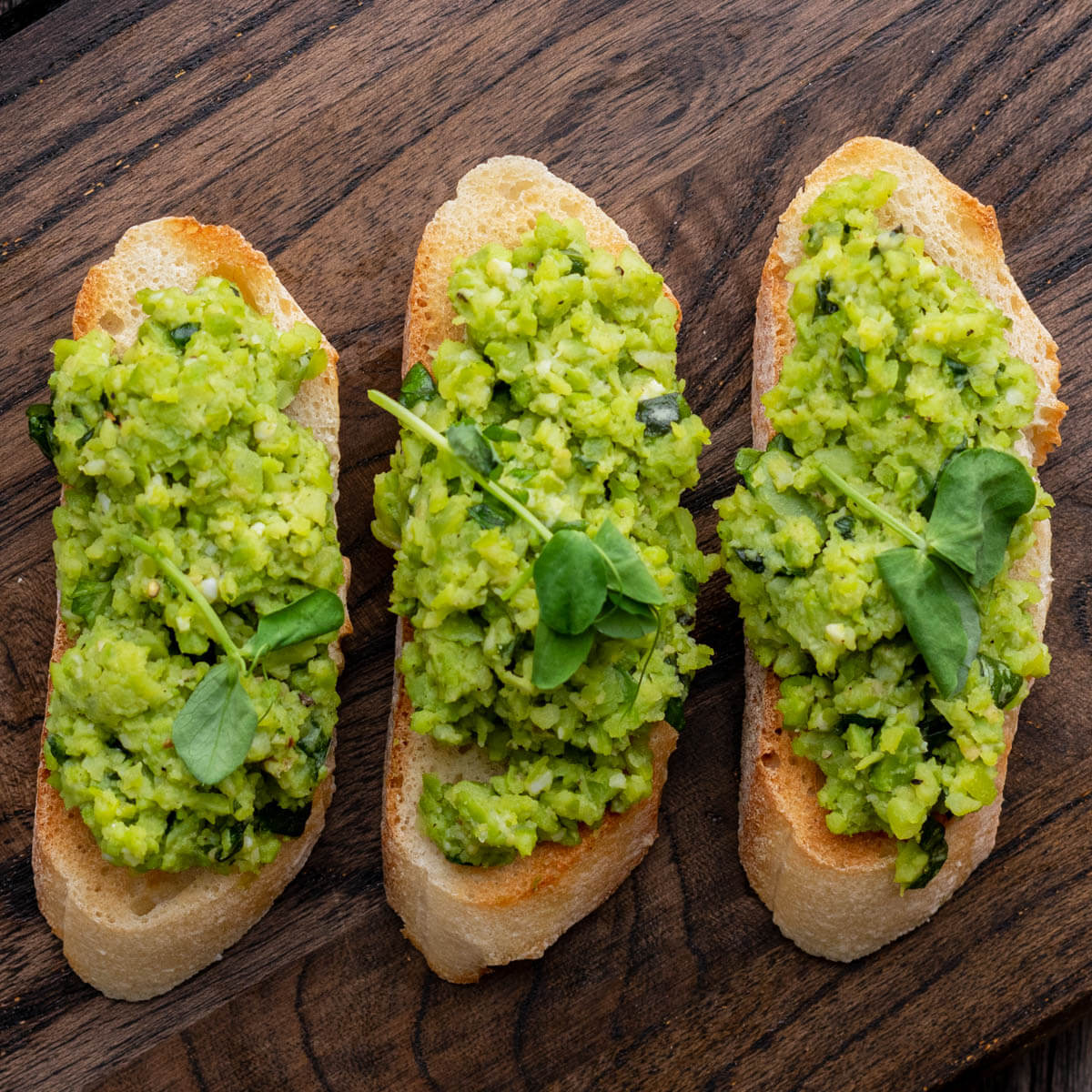Three fava bean crostini topped with bright green fava bean puree.