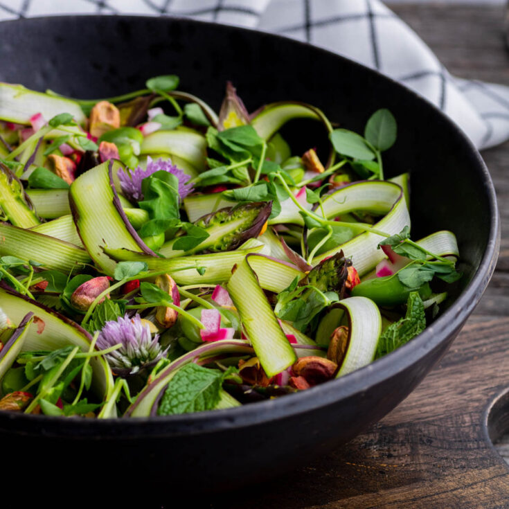 Pinterest image of a wide black bowl filled with purple and green shaved asparagus, pistachios, fava beans, fresh herbs and purple chive flowers. Topped with a white ball of burrata.