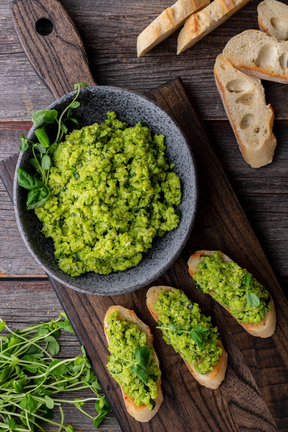 Three fava bean crostini beside a stone bowl filled with fava bean topping and sliced baguette.