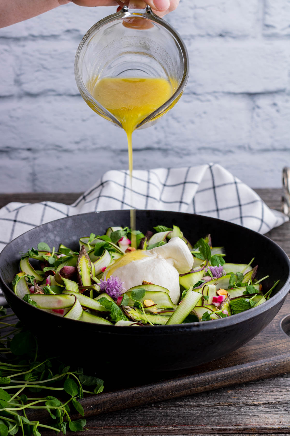 A simple mustard vinaigrette being poured over a Shaved Asparagus Salad.