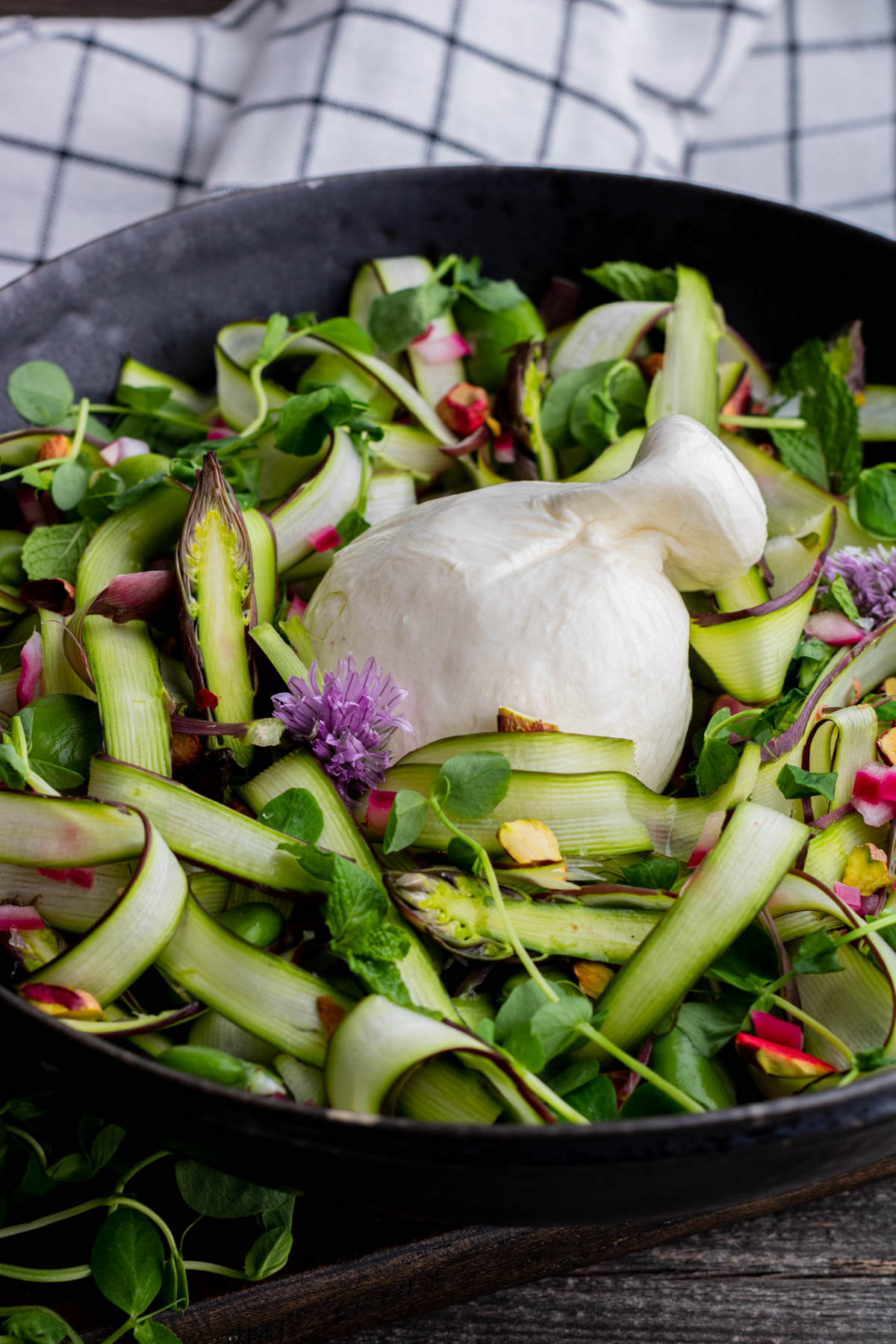 A wide black bowl filled with purple and green shaved asparagus salad, topped with a ball of fresh white burrata.