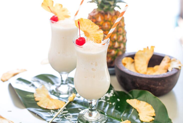 Two pina coladas in hurricane glasses surrounded by pineapple, dried pineapple wedges, and shredded coconut.