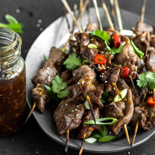 A platter of grilled Teriyaki Beef Sticks garnished with chopped green herbs and red hot peppers. A jar of teriyaki sauce on the side.