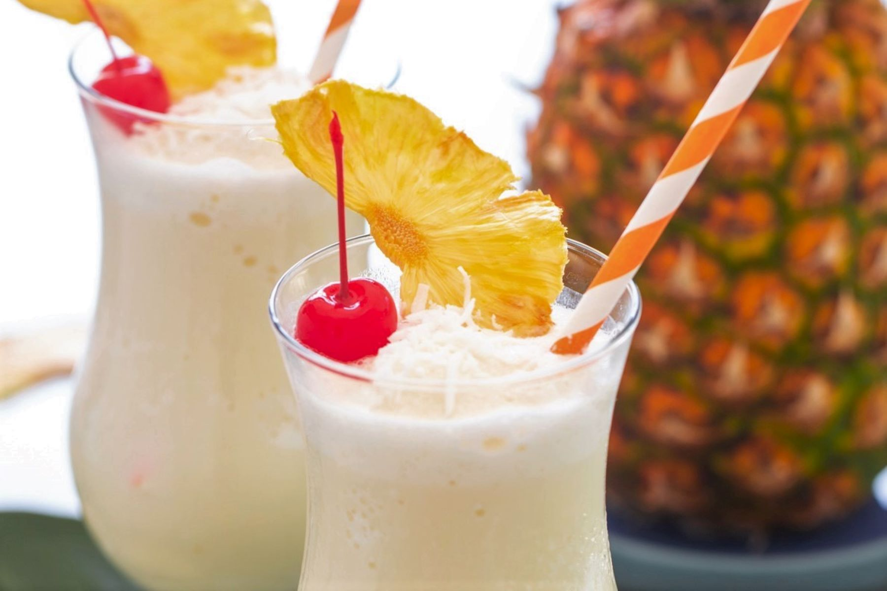 Close up of a pina colada garnished with a red cherry, dried pineapple wedge, and shredded coconut.